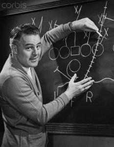 Coach explaining sports diagram on blackboard